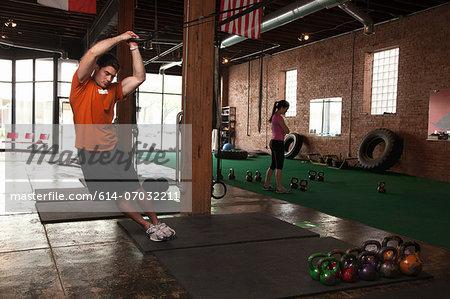 Bodybuilder using rings in gym