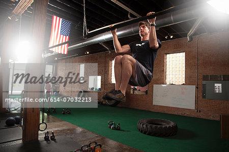 Bodybuilder doing pull up on bar in gym