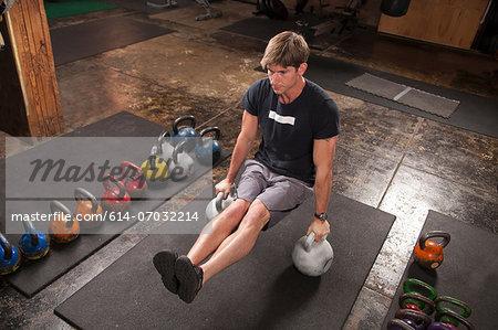 Bodybuilder on floor in gym using kettlebells