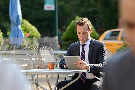 Businessman using digital tablet at sidewalk cafe