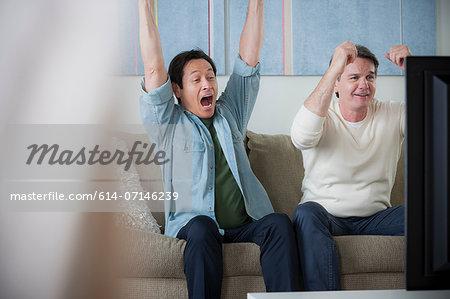 Mature men watching tv, cheering