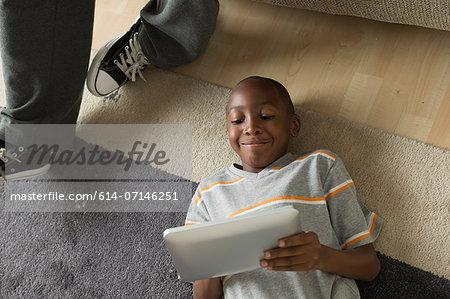 Boy lying on floor using digital tablet