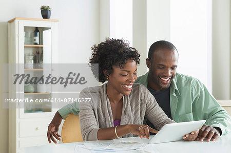 Mid adult couple using digital tablet