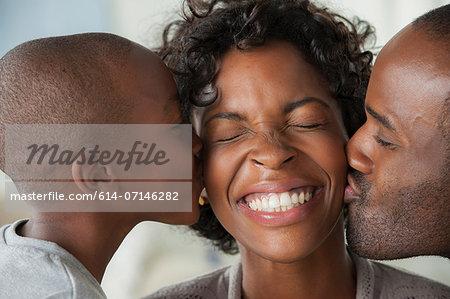 Boy and man kissing woman on cheeks