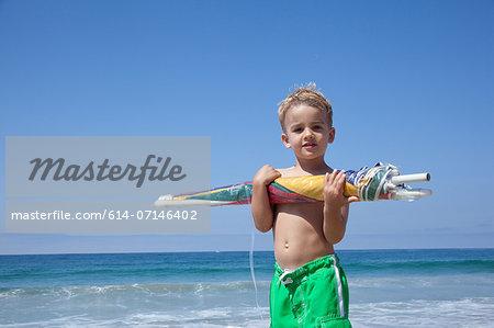 Male toddler holding sun umbrella