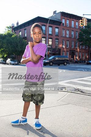 Portrait of teenage boy on sidewalk, Brooklyn, New York, USA