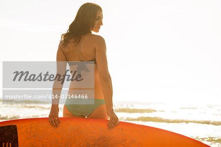 Young woman holding surfboard, La Jolla, San Diego, California, USA