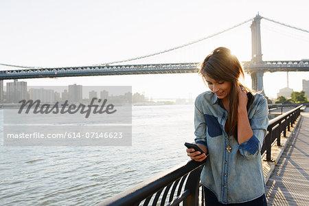 Young woman using cell phone, Manhattan Bridge, Brooklyn, USA