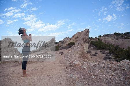 Side view of woman doing yoga at Vazquez Rocks, LA
