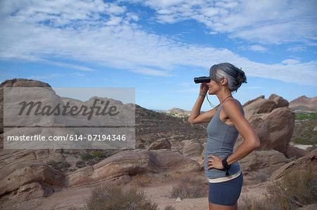 Woman standing at Vazquez Rocks looking through binoculars