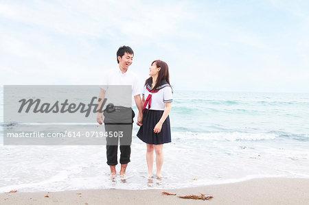 Young couple wearing school uniform standing on sandy beach