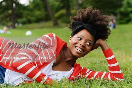 Woman lying sideways on grass