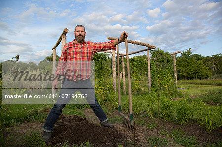 Mature man holding rake on herb farm