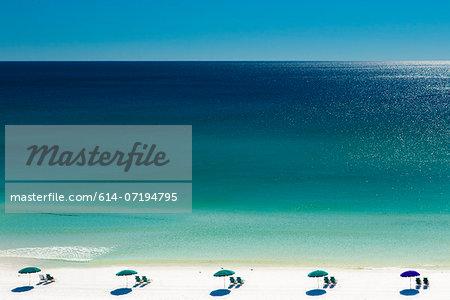 Beach umbrellas and deck chairs on beach, Destin, Florida, USA