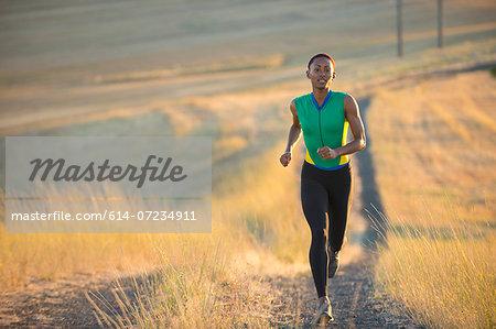 Young woman running on dirt track, Bainbridge Island, Washington State, USA