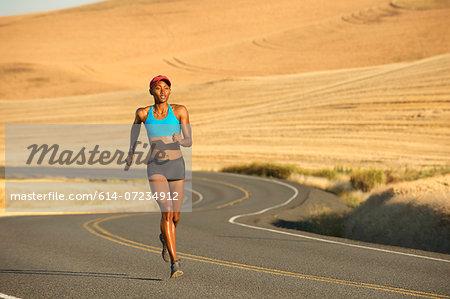 Young woman running on road, Bainbridge Island, Washington State, USA