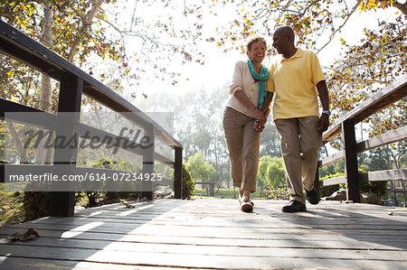 Senior couple walking on footbridge in park