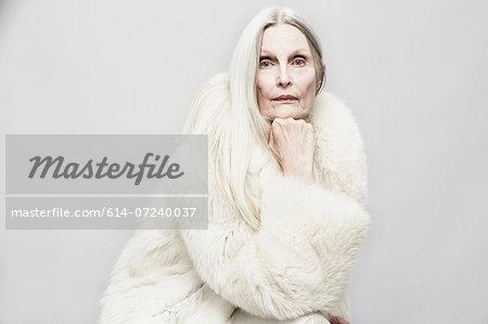 Studio portrait of senior woman with hand on chin