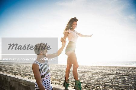 Young woman walking along wall holding boyfriend's hand for balance