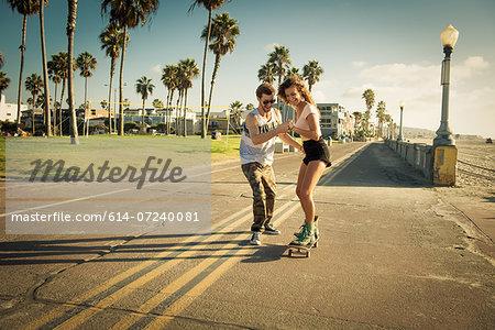 Young woman on skateboard at San Diego beach, boyfriend helping