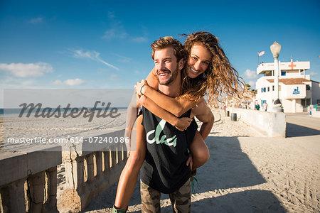 Young man giving girlfriend a piggy back at San Diego beach