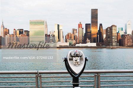 View of tourist binoculars toward East River and manhattan skyline, New York, USA