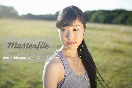 Portrait of young female runner wearing earphones