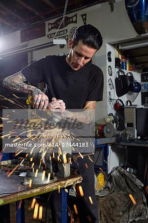 Mature man welding parts in motorcycle repair workshop