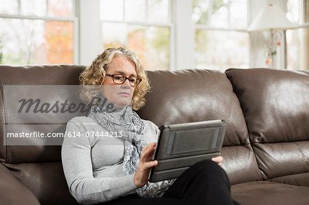 Senior woman on sofa looking at digital tablet