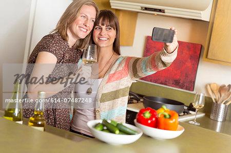 Mid adult female friends taking self portrait on smartphone in kitchen