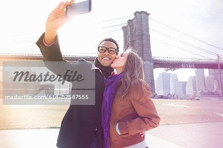 Young couple taking self portrait next to Brooklyn Bridge, New York, USA