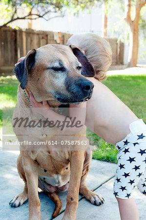 Female toddler hugging old dog