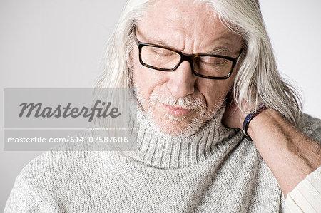 Portrait of mature man, eyes closed, hand on head