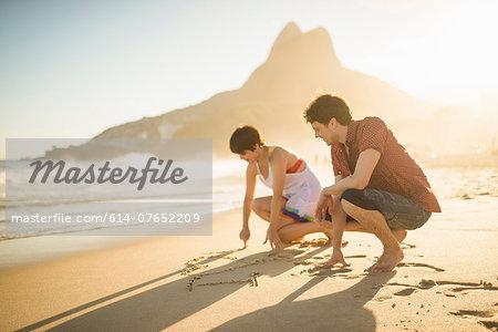 Young couple writing on sand, Ipanema Beach, Rio, Brazil
