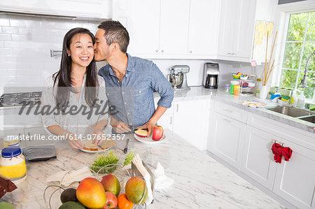 Romantic mid adult couple preparing sandwich at kitchen counter