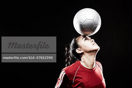 Young woman balancing football on forehead