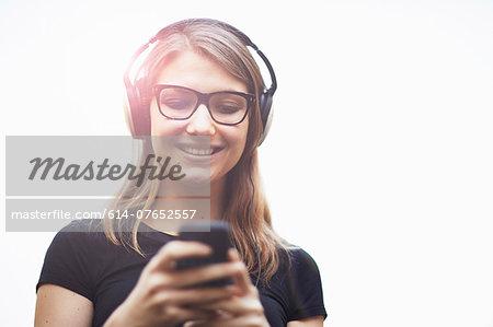 Young woman wearing headphones using smartphone