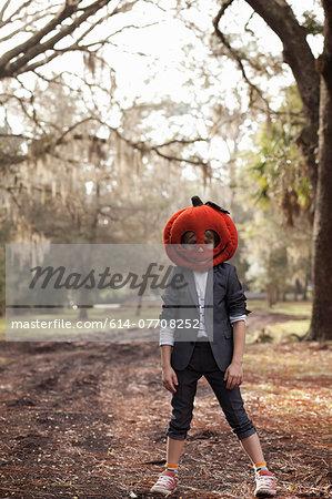 Portrait of boy in forest wearing pumpkin head