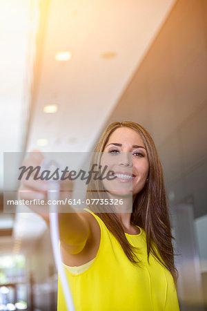 Businesswoman holding electric plug