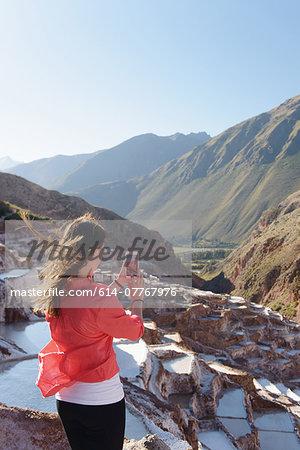 Young female tourist photographing salt pools, Maras, Peru