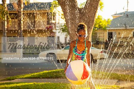 Girl with beachball in garden sprinkler