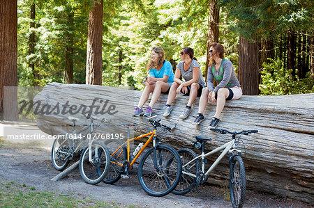 Three women mountain bikers sitting on tree trunk in forest