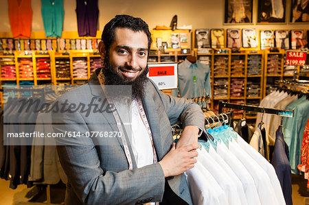 Portrait of tailor leaning against rails in men's clothes shop