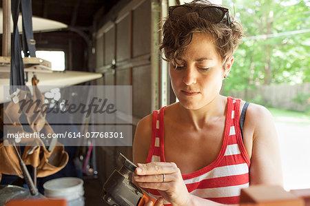Mid adult woman preparing sander to restore furniture in garage