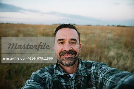 Self portrait of smiling farmer in field, Plattsburg, Missouri, USA