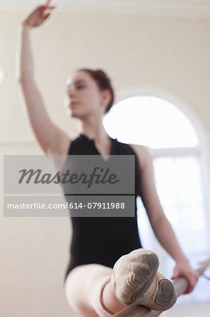 Teenage ballerina dancing at the barre in ballet school