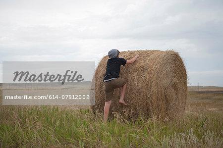 Teenage boy climbing on haystack, South Dakota, USA
