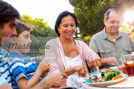 Three generation family dining in garden