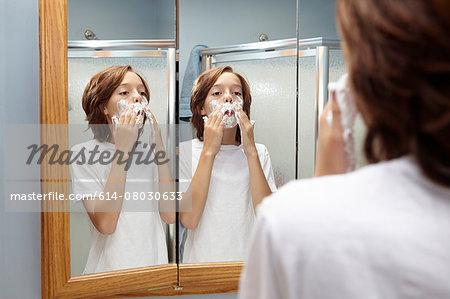Boy practicing applying shaving foam in bathroom mirror