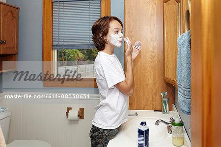 Boy applying shaving foam in bathroom mirror